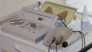 Detailaufnahme Viralfeldtherapiegerät, graue Apparatur auf Tisch mit Desinfektionsmittel und Schale